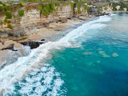 Aerial view of blue clear ocean over sandy coastline with cliff. Waves for surfing. Bali. Indonesia, holiday destination