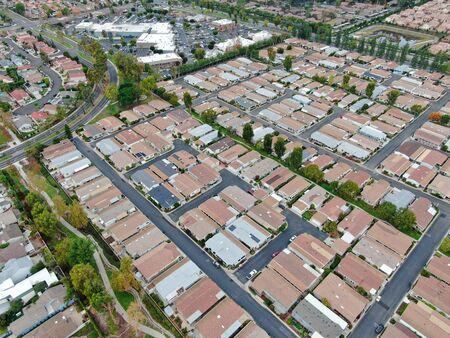 Aerial view of urban sprawl. Suburban packed homes neighborhood with road. Vast subdivision in Irvine, California, USA