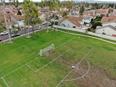 Suburban packed homes neighborhood with small park and soccer field. Vast subdivision in Irvine, California, USA