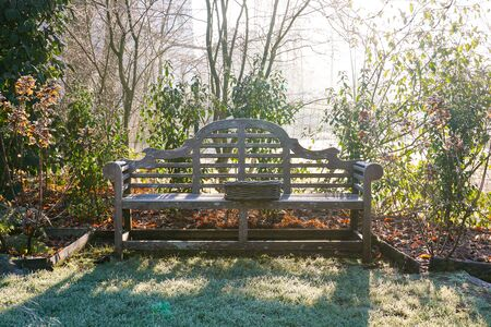 A landscape view on a winter morning in frost and sunlight of a garden with wood bench, plant borders, green frosty grass lawn brown. Stock fotó