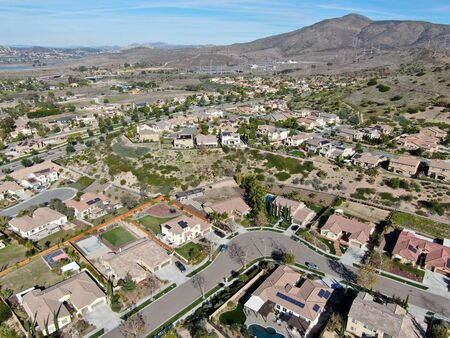 Aerial view of neighborhood with residential modern subdivision luxury houses and small road during sunny day in Chula Vista, California, USA.