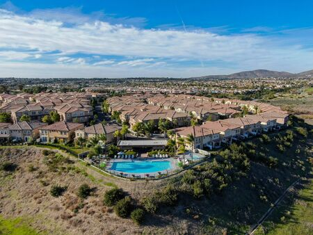 Aerial view of middle class neighborhood with identical residential subdivision house and compound swimming pool during sunny day in Chula Vista, California, USA.