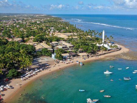 Vista aérea de la aldea de la costa de Praia Do Forte con playa y agua de mar azul clara, Bahía, Brasil. Viaje destino tropical.
