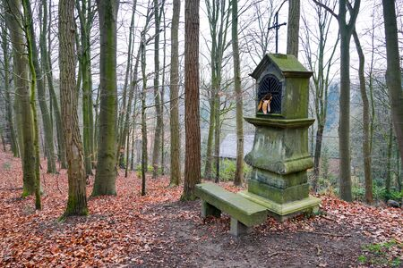 Typical old Christian wayside shrine at a country little forest in Belgium. Stock Photo
