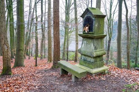 Typical old Christian wayside shrine at a country little forest in Belgium. Archivio Fotografico