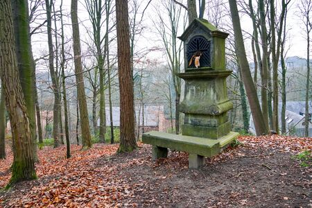 Typical old Christian wayside shrine at a country little forest in Belgium.