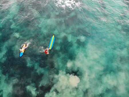 Aerial view of surfers waiting the waves in blue clear water. Surfer on the waves, surfers on their board waiting the waves, in Bali, Indonesia. Stock Photo