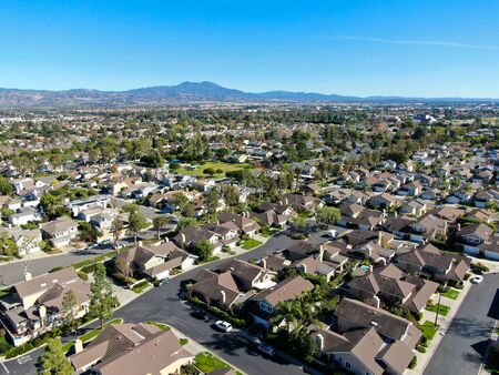 Aerial view of residential suburban packed homes neighborhood during blue sky day in Irvine, Orange County, USA Фото со стока