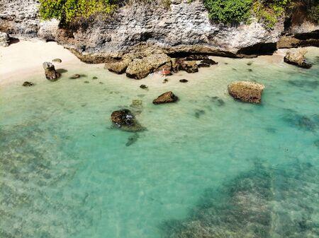 Vista aérea de una pequeña playa increíble con acantilado de roca en Bali. Hermosa agua de mar con olas para surfear. Paisaje oceánico, destino de vacaciones
