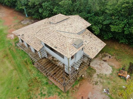 Aerial view of home type villa under construction surrounded by green garden. Exterior view of new wealthy holiday type two floor cottage in tropical country under construction.