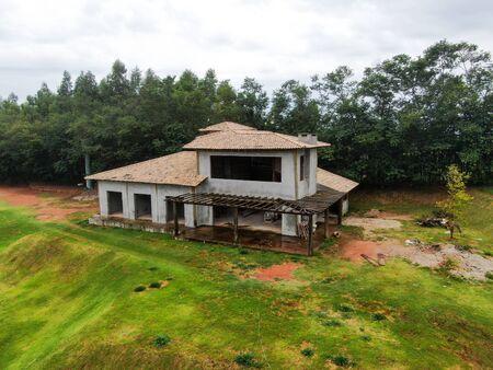 Vue aérienne de la villa de type maison en construction entourée d'un jardin verdoyant. Vue extérieure du nouveau cottage de vacances riches de type deux étages dans un pays tropical en construction.