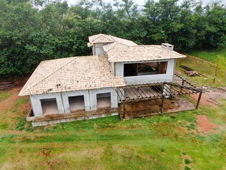 Aerial view of home type villa under construction surrounded by green garden. Exterior view of new wealthy holiday type two floor cottage in tropical country under construction. Archivio Fotografico