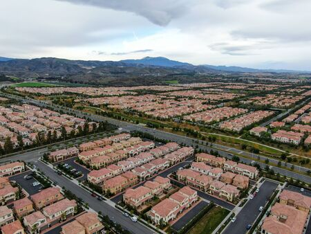 Aerial view of urban sprawl. Suburban packed homes neighborhood with road.during clouded day. Vast subdivision in Irvine, California, USA 免版税图像