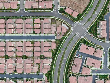 Aerial top view of urban sprawl. Suburban packed homes neighborhood with road. Vast subdivision in Irvine, California, USA