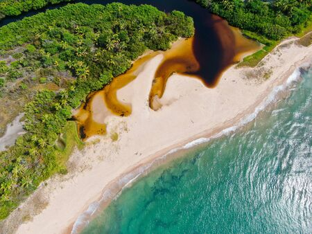 Aerial top view of river merging to tropical white sand beach and turquoise clear sea water with small waves and palm trees background. Praia do Forte, Bahia, Brazil. Travel tropical destination Stock Photo