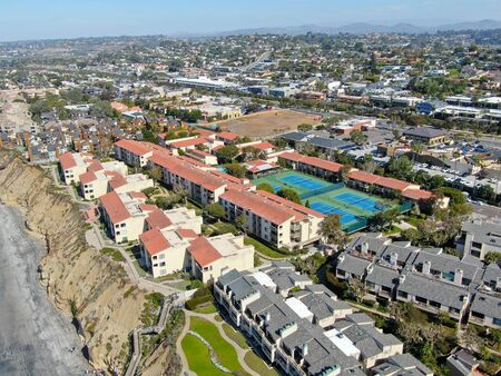 Aerial view of typical south california community condo with tennis court and pool next to the sea on the edge of the cliff during sunny day. Solana Beach. USA Stock Photo