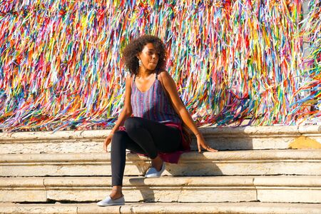Tourist poses for a photo in front of Igreja de Nosso Senhor do Bonfim, a catholic church located in Salvador, Bahia in Brazil. Famous touristic place where people make wishes while tie the ribbons in front of the church. February 22nd, 2019 Publikacyjne