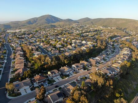 Aerial view of residential modern subdivision house neighborhood with mountain on the background during sunset time. South California, USA