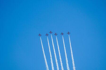 Aerobatic plane with white smoke in the blue sky, California, USA.