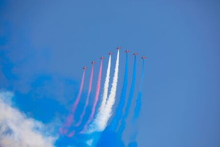 Aerobatic plane with colorful americcan flag smoke in the blue sky, California, USA. Stock Photo