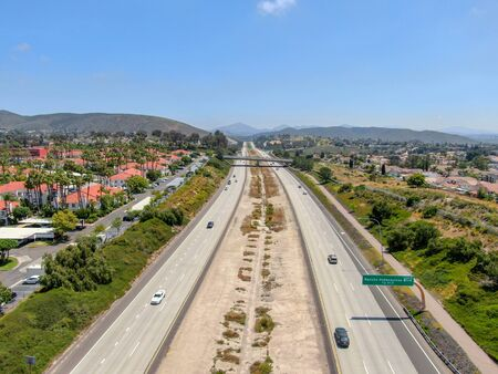 Aerial view of highway surrounded by villa in suburb. Intersection city transport road with vehicle movement. California, USA. Фото со стока
