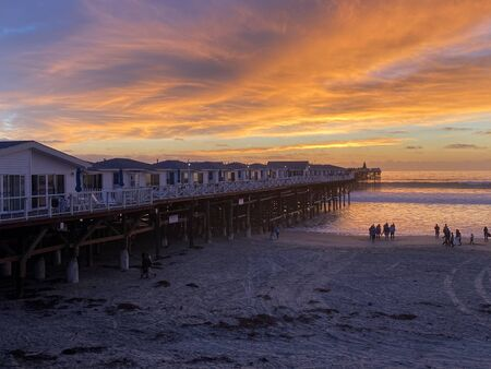 Pacific beach shoreline and pier during colorful sunset., San Diego, California, USA
