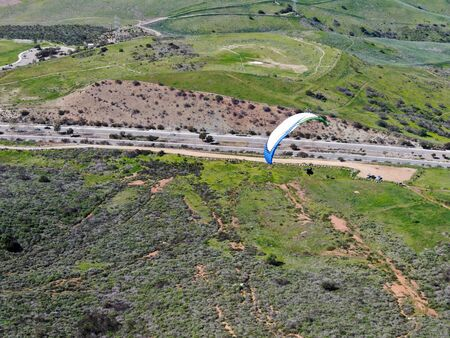 Para-glider over the top of the mountain during summer sunny day. Para-glider on the para-plane, strops -soaring flight moment flying over Black Mountain in San Diego, California. USA. February 22nd, 2020
