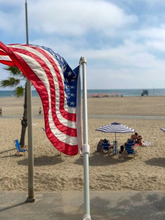 American flag with the beach on the background in Santa Monica beach, California, USA. Archivio Fotografico