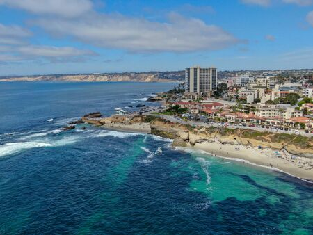 Aerial view of La Jolla coast, San Diego, California. Beach and blue sea with small waves. Hilly seaside of curving coastline along the Pacific.
