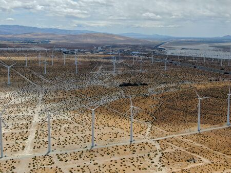 Aerial view of huge array of gigantic wind turbines spreading over the desert in Palm Springs wind farm. California. USA. Aerial view of wind turbines generating electricity.