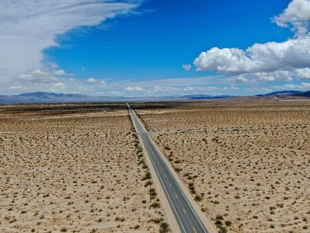 Aerial view of endless desert straight dusty asphalt road in Joshua Tree Park. USA. Long straight tarmac road heading into the desert to the direction of Arizona.