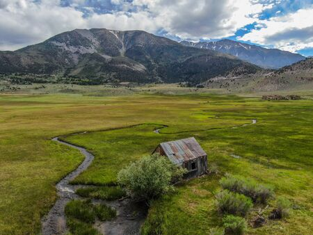 Aerial view of abandoned little small wooden house barn next small river in the green valley of a mountain, Aspen Spring, Mono County, California, USA. Imagens