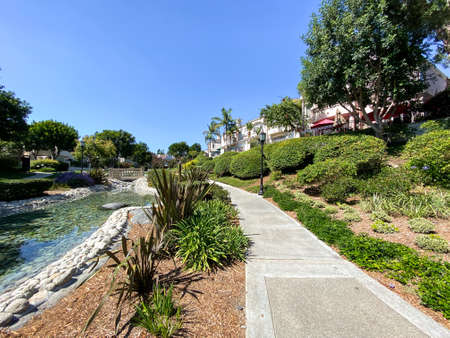 Public Park with green garden and landscape design with water pond and small water stream surrounded by villa in La Jolla, California. USA