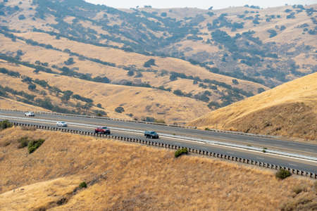 Freeway road with cars crossing the the San Luis Reservoir valleys during dry and hot season, San Luis Creek in the eastern slopes of the Diablo Range of Merced County, California. USA
