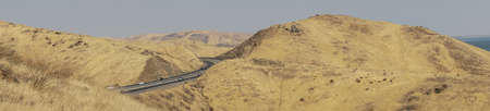 Panoramic view of the freeway road with cars crossing the the San Luis Reservoir valleys during dry season, San Luis Creek in the eastern slopes of the Diablo Range of Merced County, California. USA Stock Photo
