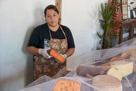 Vendor serving variety of traditional cheese in a cheese farm store, Fazenda Atalaia Cheese Farm, Amparo, State of Sao Paulo, Brazil. October 3rd, 2020 Redakční