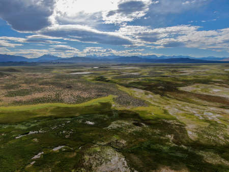 Aerial view of Long Valley next to Mammoth Lakes, Mono County, California. USA. Green grassland with mountain on the background during summer season.