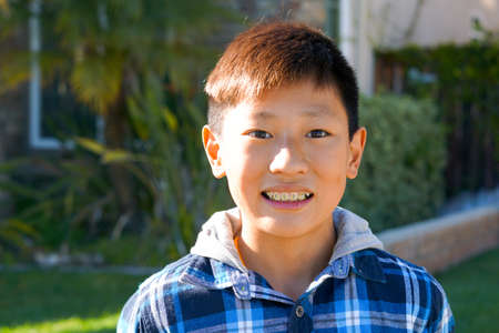 Portrait of young Asian boy with tooth braces. Young teen boy smiling and showing his orthodontic braces on his teeth.