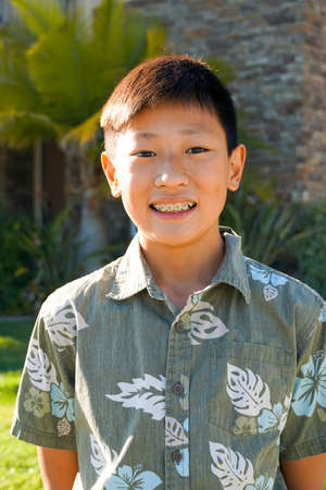 Portrait of young Asian boy with tooth braces. Young teen boy smiling and showing his orthodontic braces on his teeth. Stock Photo