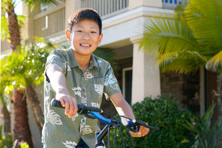 Young Asian boy on his bike in front of the house. Young teen boy on his bike smiling and showing his orthodontic braces on his teeth.