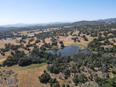 Aerial view of small lake in the valley, between farmland and forest in the town of Julian, east of San Diego, California, USA