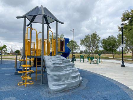 Children playground activities in public park. Slide, swing on modern playground. Urban neighborhood childhood concept. Archivio Fotografico