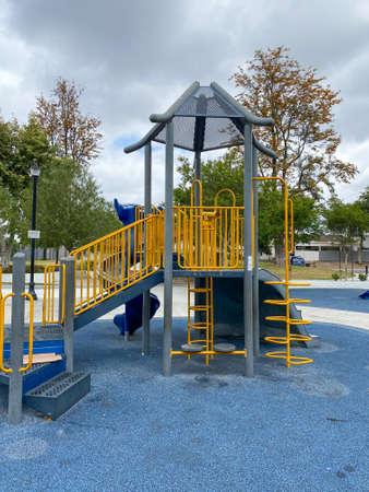 Slide, swing on modern playground. Children playground activities in public park. Urban neighborhood childhood concept.
