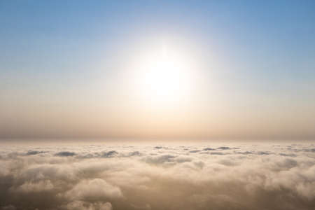 Aerial sunset view over the cloud facing the sun. Scenic view above the clouds
