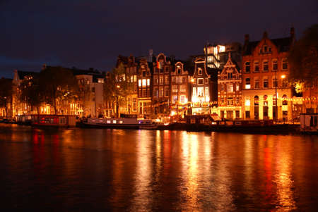 Night view of Amsterdam, Holland, with an illuminated canal and house.