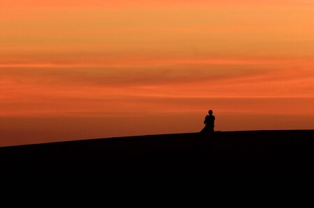 Silhouette of a man praying in the desert at sunset. Stock Photo