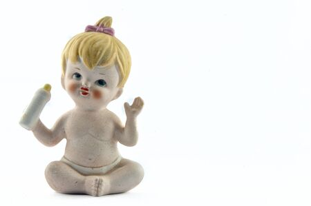 ceramic bottle: A ceramic doll Represents a blonde baby sitting and handing a baby bottle