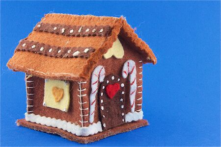 ornamentations: Funny little house made of cloth with candy canes and hearts on a blue background Stock Photo