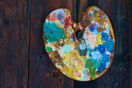 tempera: A colorful palette with dry tempera colors on it, hung on a wood wall.