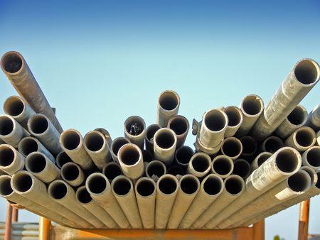 Scaffold poles on a rack set against a blue sky